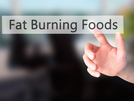 fat burning: Fat Burning Foods - Hand pressing a button on blurred background concept . Business, technology, internet concept. Stock Photo Stock Photo