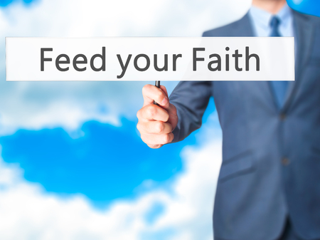 hand holding sign: Feed your Faith - Businessman hand holding sign. Business, technology, internet concept. Stock Photo