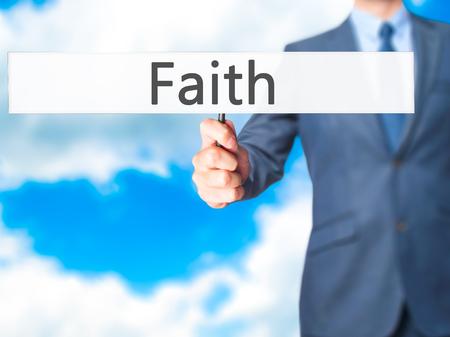 hopefulness: Faith - Businessman hand holding sign. Business, technology, internet concept. Stock Photo