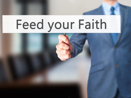 christian trust: Feed your Faith - Businessman hand holding sign. Business, technology, internet concept. Stock Photo