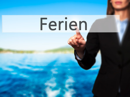 rescheduling: Ferien (Vacation in German) - Businesswoman hand pressing button on touch screen interface. Business, technology, internet concept. Stock Photo Stock Photo
