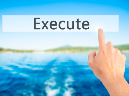 execute: Execute - Hand pressing a button on blurred background concept . Business, technology, internet concept. Stock Photo Stock Photo