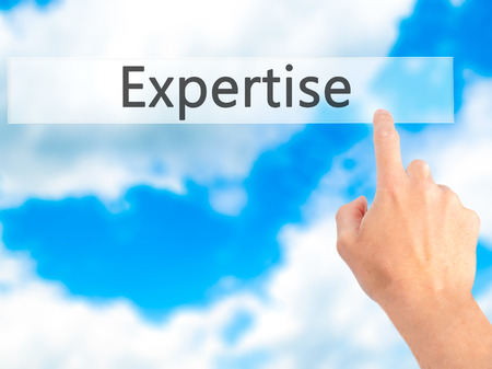expertise concept: Expertise - Hand pressing a button on blurred background concept . Business, technology, internet concept. Stock Photo