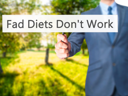 don't care: Fad Diets Dont Work - Businessman hand holding sign. Business, technology, internet concept. Stock Photo
