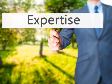 expertise concept: Expertise - Businessman hand holding sign. Business, technology, internet concept. Stock Photo