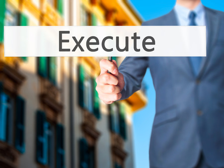 execute: Execute - Businessman hand holding sign. Business, technology, internet concept. Stock Photo