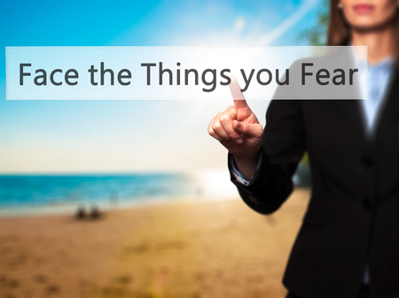beliefs: Face the Things you Fear - Businesswoman hand pressing button on touch screen interface. Business, technology, internet concept. Stock Photo