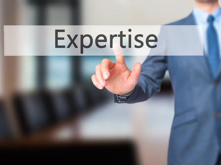 expertise concept: Expertise - Businessman hand pressing button on touch screen interface. Business, technology, internet concept. Stock Photo