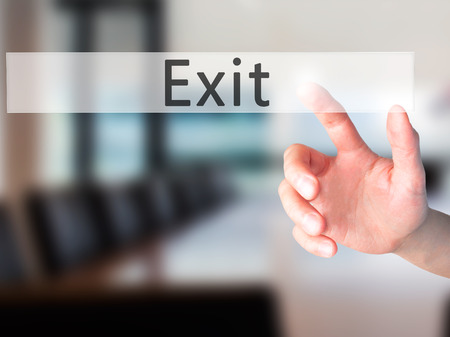 downsize: Exit - Hand pressing a button on blurred background concept . Business, technology, internet concept. Stock Photo
