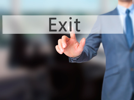 downsize: Exit - Businessman hand pressing button on touch screen interface. Business, technology, internet concept. Stock Photo