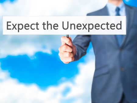 unanticipated: Expect the Unexpected - Businessman hand holding sign. Business, technology, internet concept. Stock Photo