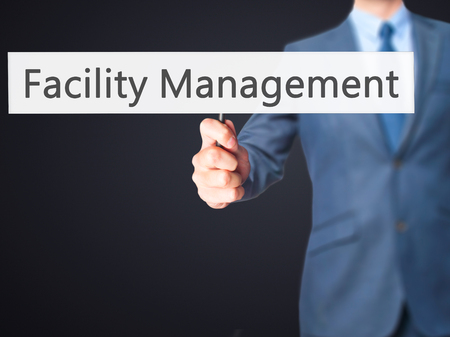 dwell house: Facility Management - Businessman hand holding sign. Business, technology, internet concept. Stock Photo Stock Photo