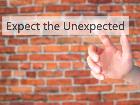 unexpected: Expect the Unexpected - Hand pressing a button on blurred background concept . Business, technology, internet concept. Stock Photo