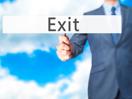 downsize: Exit - Businessman hand holding sign. Business, technology, internet concept. Stock Photo