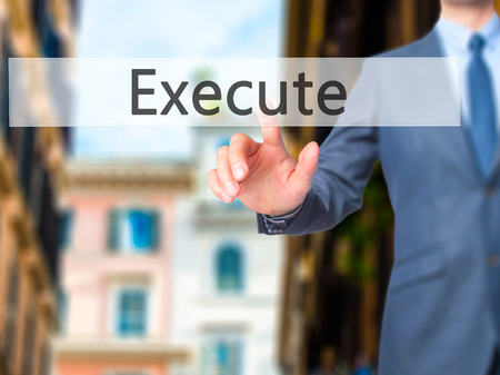 execute: Execute - Businessman hand pressing button on touch screen interface. Business, technology, internet concept. Stock Photo Stock Photo