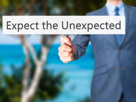suddenness: Expect the Unexpected - Businessman hand holding sign. Business, technology, internet concept. Stock Photo