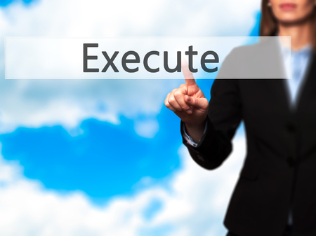 execute: Execute - Businesswoman hand pressing button on touch screen interface. Business, technology, internet concept. Stock Photo