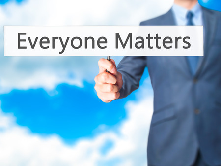 everyone: Everyone Matters - Businessman hand holding sign. Business, technology, internet concept. Stock Photo