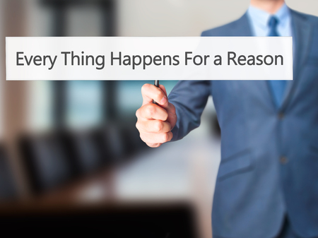 happens: Every Thing Happens For a Reason - Businessman hand holding sign. Business, technology, internet concept. Stock Photo
