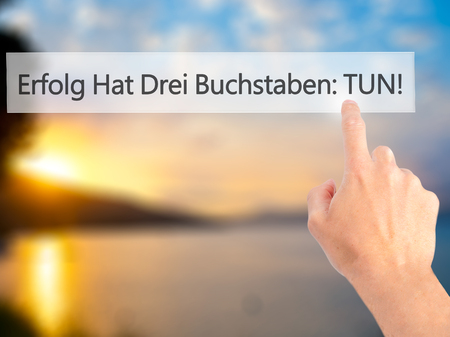 buchstaben: Erfolg Hat Drei Buchstaben: Tun! (Success Has Three Letters: Do in German) - Hand pressing a button on blurred background concept . Business, technology, internet concept. Stock Photo