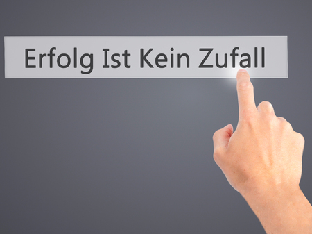 ist: Erfolg Ist Kein Zaufall (Success Is No Accident in German) - Hand pressing a button on blurred background concept . Business, technology, internet concept. Stock Photo