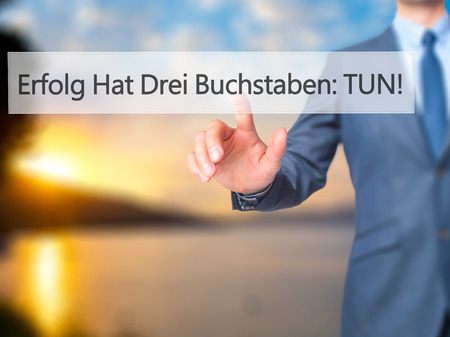 buchstaben: Erfolg Hat Drei Buchstaben: Tun! (Success Has Three Letters: Do in German) - Businessman hand pressing button on touch screen interface. Business, technology, internet concept. Stock Photo