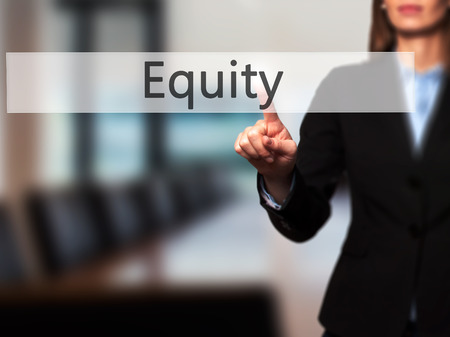 equidad: Equity - Businesswoman hand pressing button on touch screen interface. Business, technology, internet concept. Stock Photo Foto de archivo