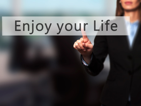 just ahead: Enjoy your Life - Businesswoman hand pressing button on touch screen interface. Business, technology, internet concept. Stock Photo Stock Photo