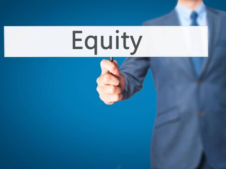 equity: Equity - Businessman hand holding sign. Business, technology, internet concept. Stock Photo
