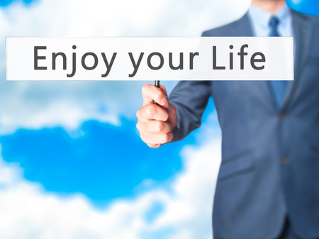 just ahead: Enjoy your Life - Businessman hand holding sign. Business, technology, internet concept. Stock Photo Stock Photo