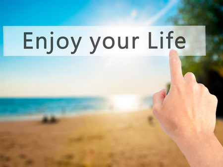 just ahead: Enjoy your Life - Hand pressing a button on blurred background concept . Business, technology, internet concept. Stock Photo Stock Photo