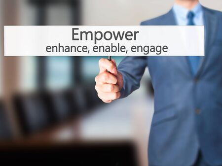 enable: Empower enhance, enable, engage - Businessman hand holding sign. Business, technology, internet concept. Stock Photo