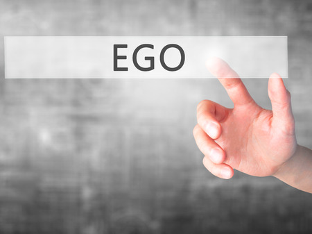 ego: Ego - Hand pressing a button on blurred background concept . Business, technology, internet concept. Stock Photo