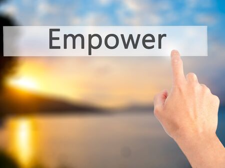empower: Empower - Hand pressing a button on blurred background concept . Business, technology, internet concept. Stock Photo