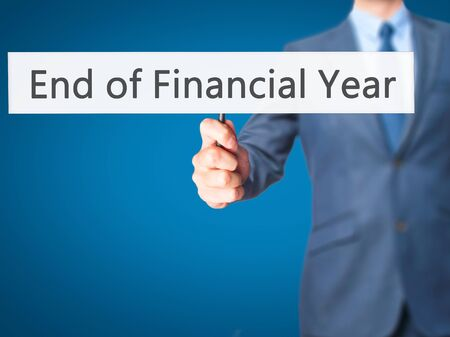 end of year: End of Financial Year - Businessman hand holding sign. Business, technology, internet concept. Stock Photo