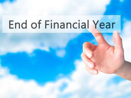 year financial statements: End of Financial Year - Hand pressing a button on blurred background concept . Business, technology, internet concept. Stock Photo Stock Photo
