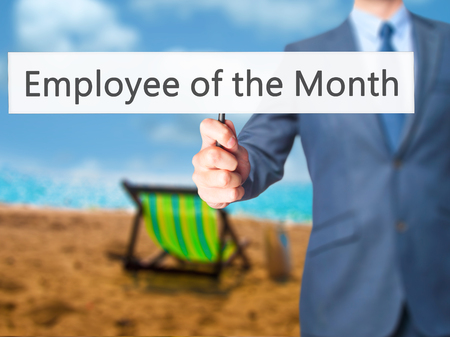 recognizing: Employee of the Month - Businessman hand holding sign. Business, technology, internet concept. Stock Photo