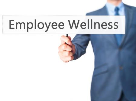 Employee Wellness - Businessman hand holding sign. Business, technology, internet concept. Stock Photo