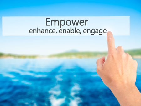enable: Empower enhance, enable, engage - Hand pressing a button on blurred background concept . Business, technology, internet concept. Stock Photo
