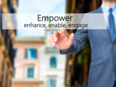 decisionmaking: Empower enhance, enable, engage - Businessman hand pressing button on touch screen interface. Business, technology, internet concept. Stock Photo