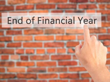 End of Financial Year - Hand pressing a button on blurred background concept . Business, technology, internet concept. Stock Photo Stock Photo