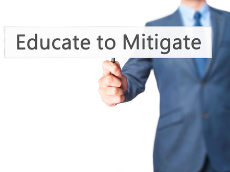 Educate to Mitigate - Businessman hand holding sign. Business, technology, internet concept. Stock Photo Stock Photo