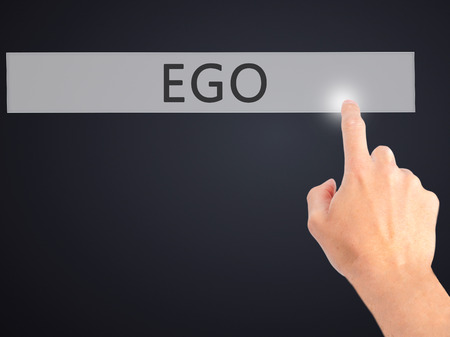 egoista: Ego - Hand pressing a button on blurred background concept . Business, technology, internet concept. Stock Photo