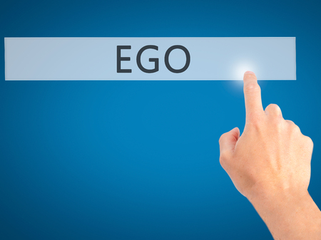 pompous: Ego - Hand pressing a button on blurred background concept . Business, technology, internet concept. Stock Photo
