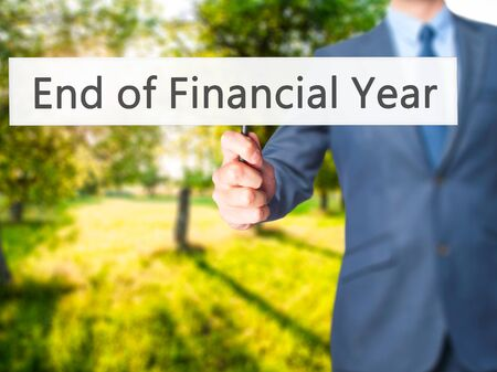year financial statements: End of Financial Year - Businessman hand holding sign. Business, technology, internet concept. Stock Photo