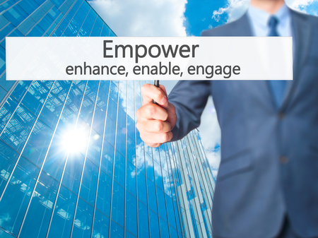 decisionmaking: Empower enhance, enable, engage - Businessman hand holding sign. Business, technology, internet concept. Stock Photo