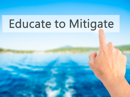 mitigate: Educate to Mitigate - Hand pressing a button on blurred background concept . Business, technology, internet concept. Stock Photo