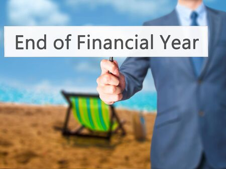 End of Financial Year - Businessman hand holding sign. Business, technology, internet concept. Stock Photo