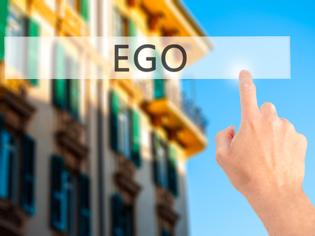 selfish: Ego - Hand pressing a button on blurred background concept . Business, technology, internet concept. Stock Photo