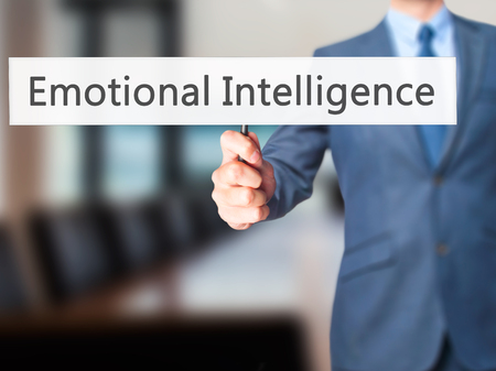 continence: Emotional Intelligence - Businessman hand holding sign. Business, technology, internet concept. Stock Photo Stock Photo